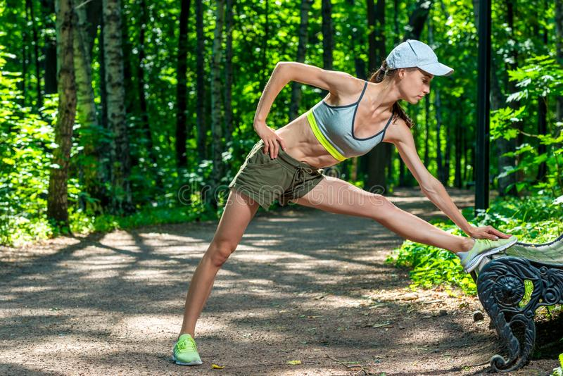 athletic girl warms up her muscles before jogging royalty free stock photos