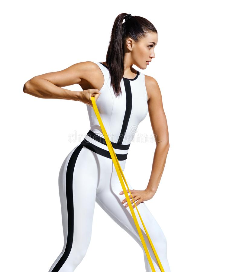 Athletic girl working with resistance band. Photo of attractive latin girl with beautiful athletic body isolated on white background. Strength and motivation stock photography