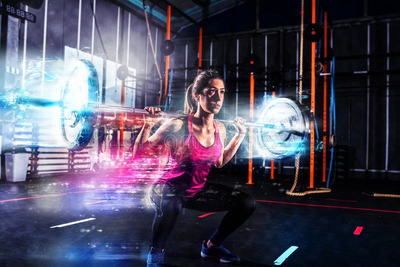 Athletic girl works out at the gym with a barbell with blue energy effects royalty free stock photography