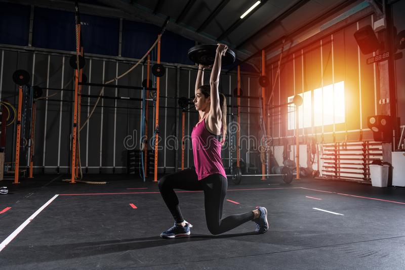 Athletic girl works out at the gym with a barbell disk stock photography