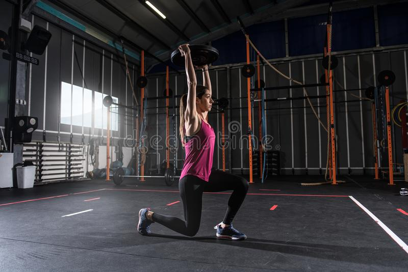 Athletic girl works out at the gym with a barbell disk stock photo