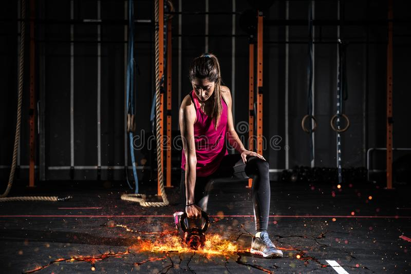 Athletic girl works out at the gym with a fiery kettlebell royalty free stock photos