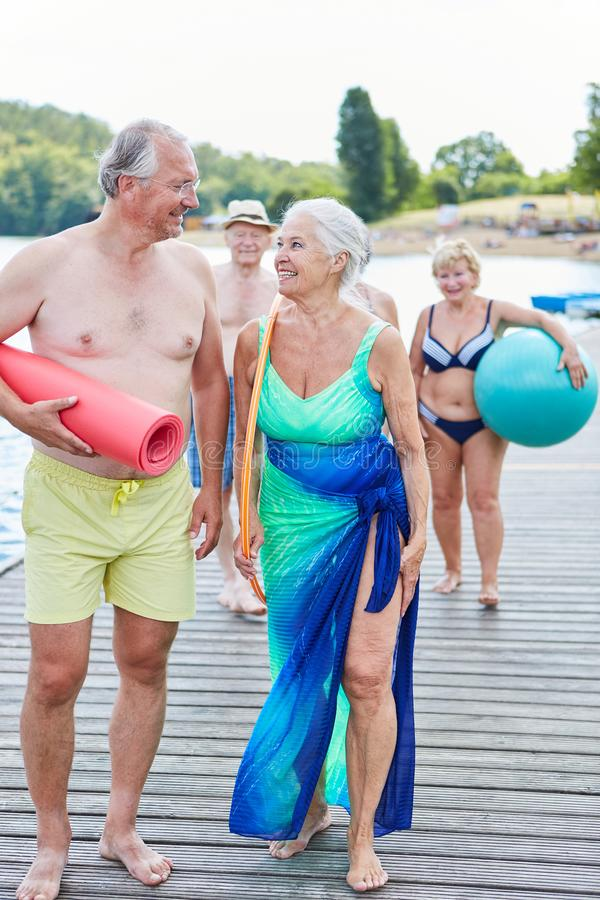 Sporting group seniors on vacation. Athletic group seniors on vacation is taking a walk on the lake in summer stock image
