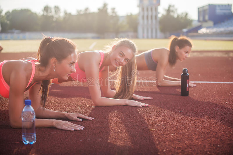 Athletic group of women training on a sunny day doing planking exercise in the stadium. stock photo