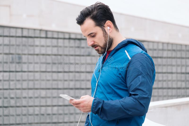 Athletic guy doing training session with smartphone royalty free stock images