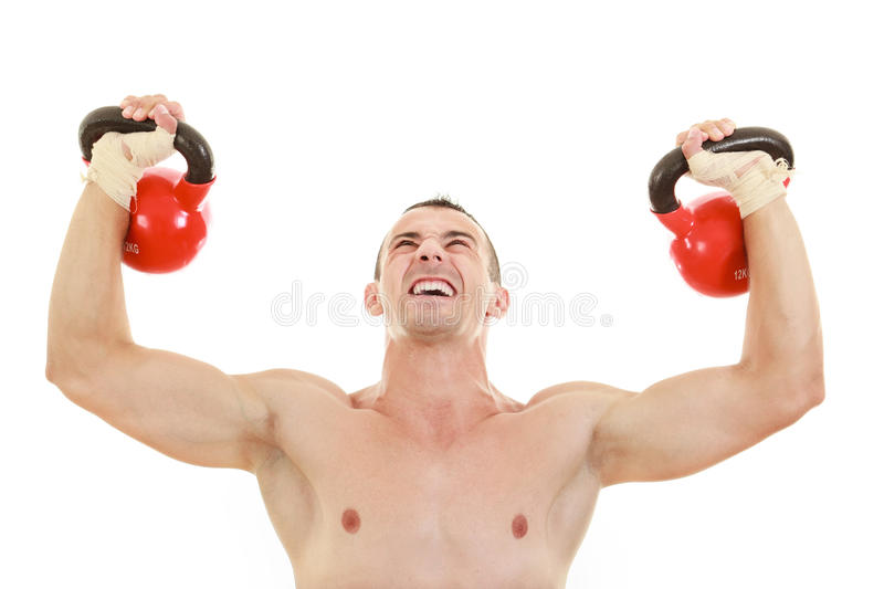 athletic half naked man holding and lifting red kettlebells weights royalty free stock photo