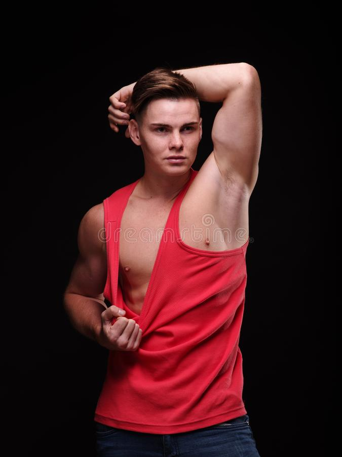 Healthy, beautiful, young man pulling his red t-shirt on a black background. Sporty lifestyle concept. stock photography