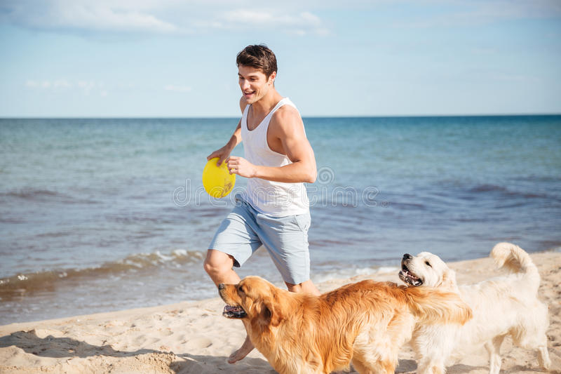 Athletic handsome man playing with his dog on the beach royalty free stock images