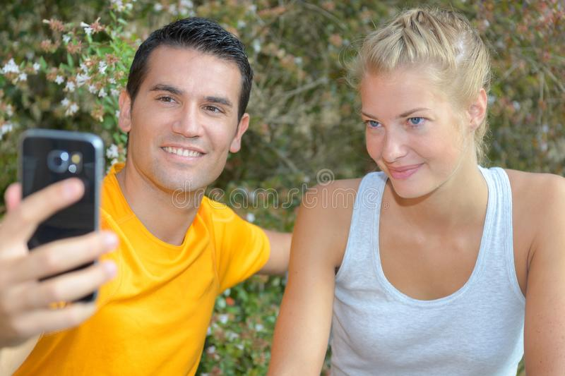 Athletic healthy cheerful couple making selfie after training royalty free stock images