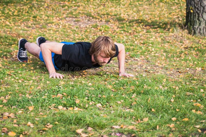 Athletic hipster man is doing push-ups in the park. Athletic hipster man doing exercises in the park. Caucasian young man is doing push-ups exercises.The sport stock photos
