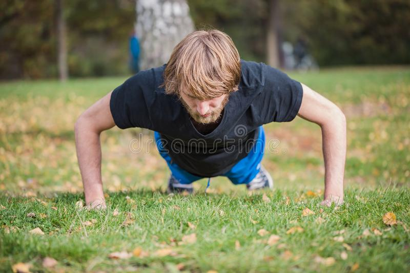 Athletic hipster man is doing push-ups in the park. Athletic hipster man doing exercises in the park. Caucasian young man is doing push-ups exercises.The sport stock photography