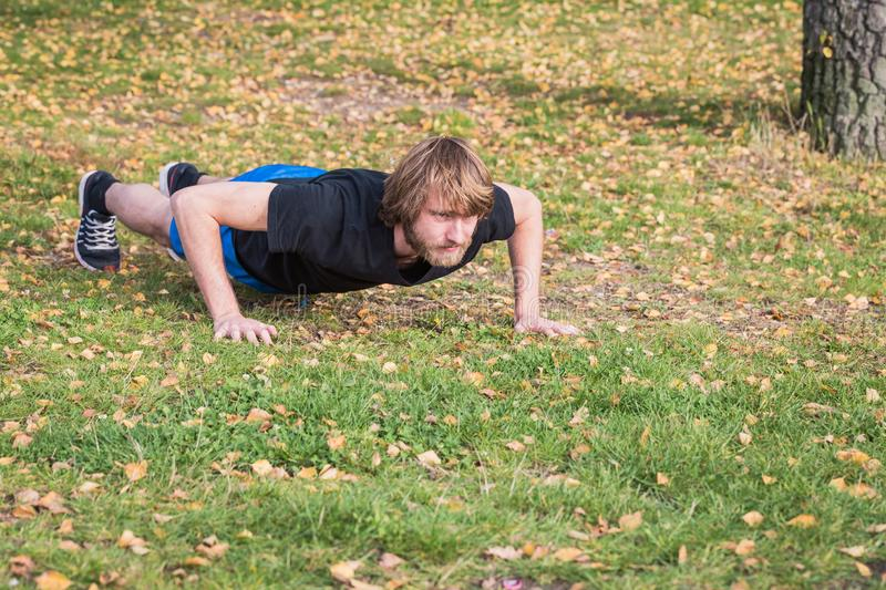 Athletic hipster man is doing push-ups in the park. Athletic hipster man doing exercises in the park. Caucasian young man is doing push-ups exercises.The sport stock image