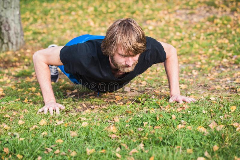 Athletic hipster man is doing push-ups in the park. Athletic hipster man doing exercises in the park. Caucasian young man is doing push-ups exercises.The sport royalty free stock photo