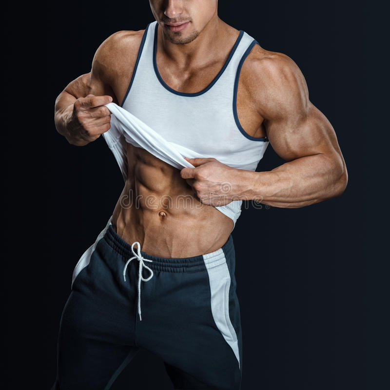 Athletic male model posing, pulling up tank top. Athletic male model posing in sports clothing, pulling up tank top to reveal fit muscular abs. on black stock images