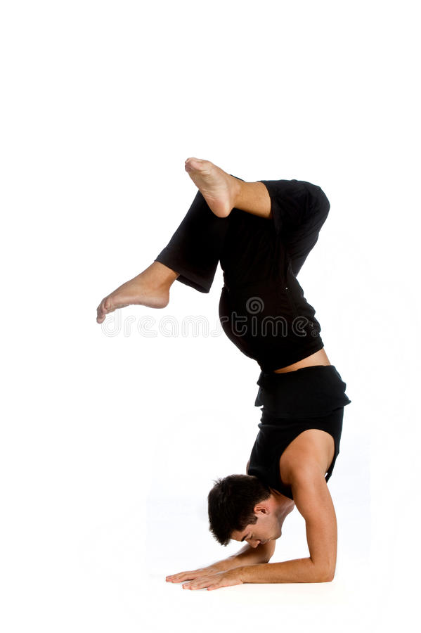 Athletic Man. An athletic man doing a handstand against white background stock image
