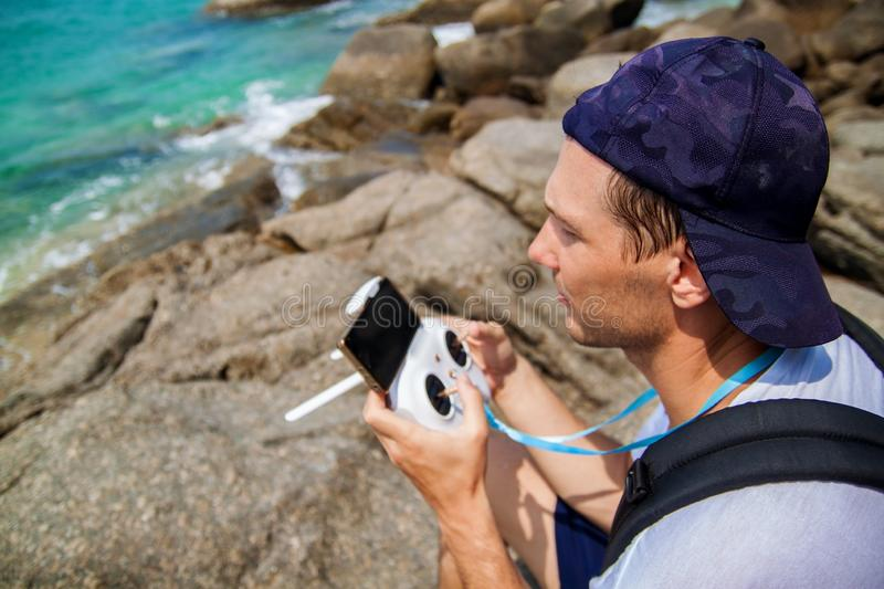 Man operating a drone with remote control on beach. royalty free stock image