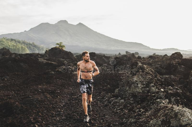 Athletic man with beard trail running outdoors stock image