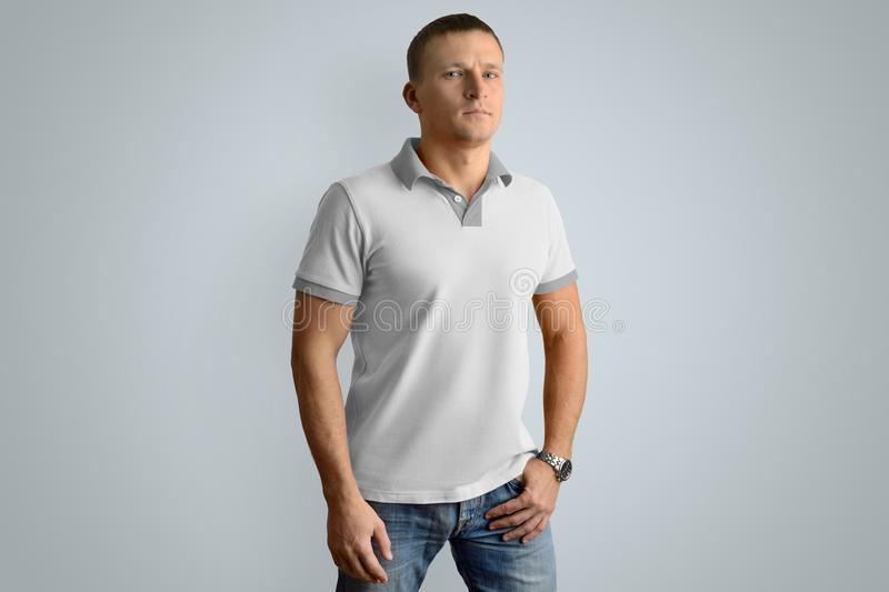 Athletic man in the blank polo shirt. Mockup for your design or. Athletic man in the blank polo shirt and blue jeans with hand in the pocket isolated on the gray royalty free stock photography