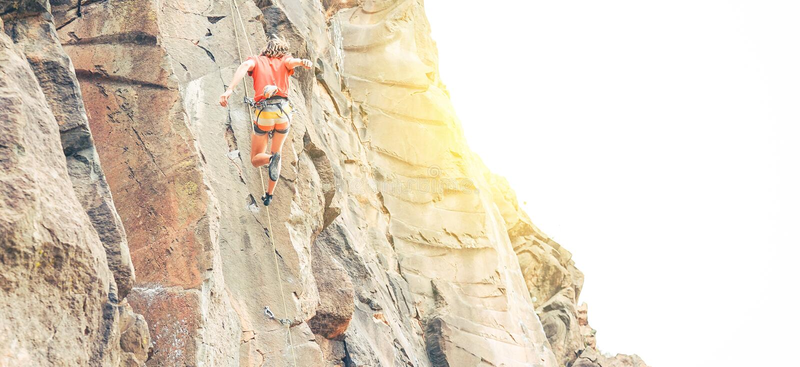 Athletic man clambing a rock wall at sunset - Climber performing on a canyon mountain making an acrobatic jump royalty free stock photo