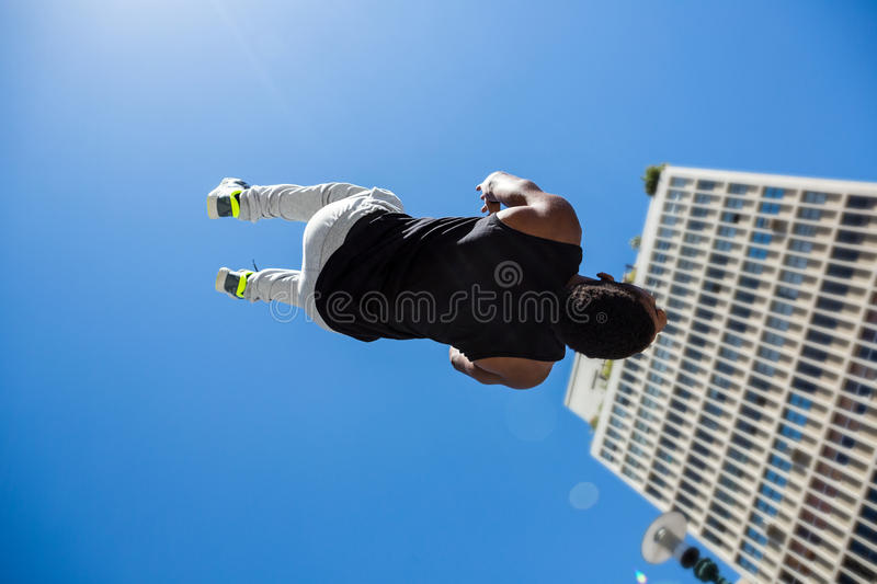 Athletic man doing back flip in the city. On a sunny day stock photos