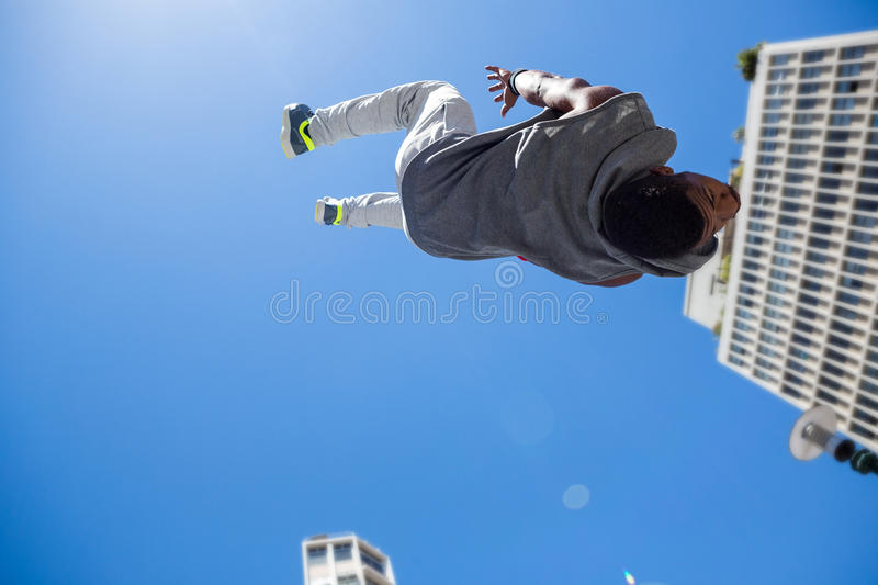 Athletic man doing back flip in the city. On a sunny day stock photo