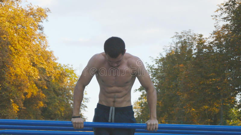 Athletic man doing push ups on parallel bars at sports ground in city park. Strong young muscular guy training outdoor royalty free stock photography