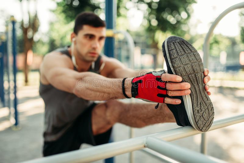 Athletic man doing stretching exercise outdoor stock images