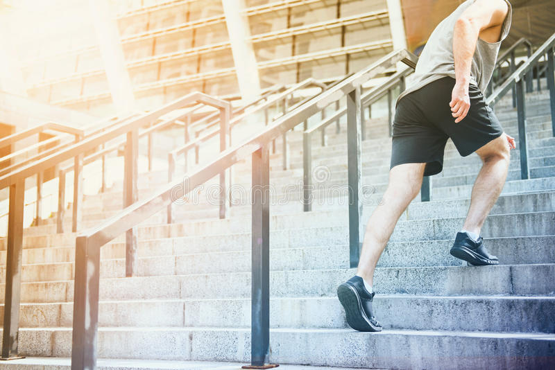 Athletic man going to stadium up the stairs stock photo