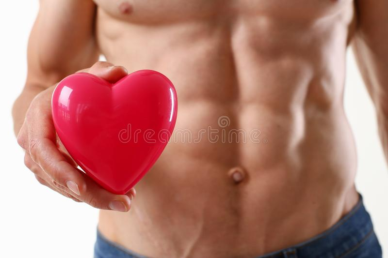 Athletic man holds a red heart in his hand royalty free stock photos