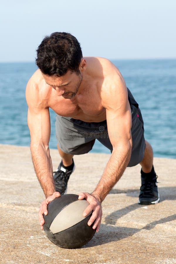 Athletic man making push-ups on abdominal ball. Training at sea side royalty free stock photo