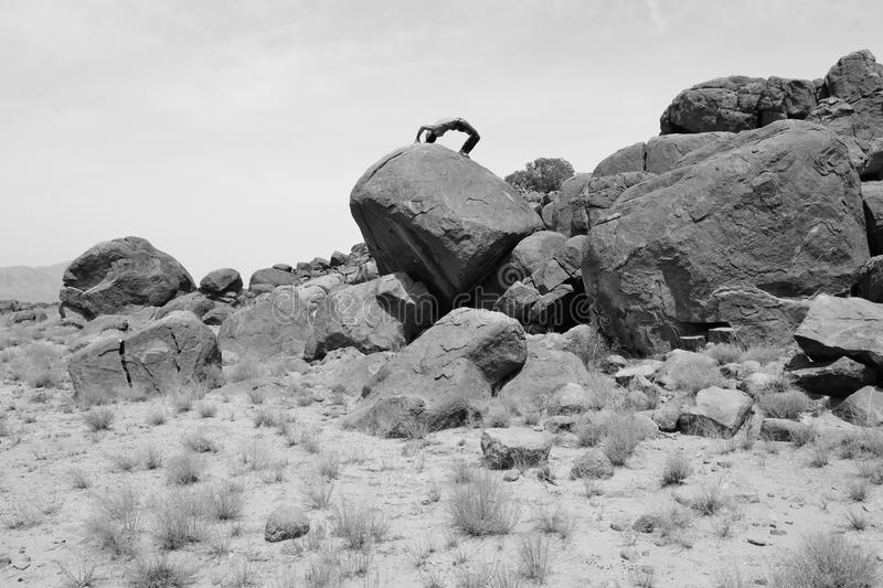 Athletic man on a pile of rocks -B&W- stock photos