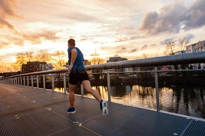 Athletic man practicing sport outdoors. Young athletic man practicing sport outdoors, running fast along bridge over the sunset sky background. Self overcome stock photo