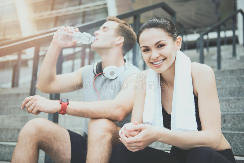 Athletic man and pretty girl sitting near stadium together stock photos