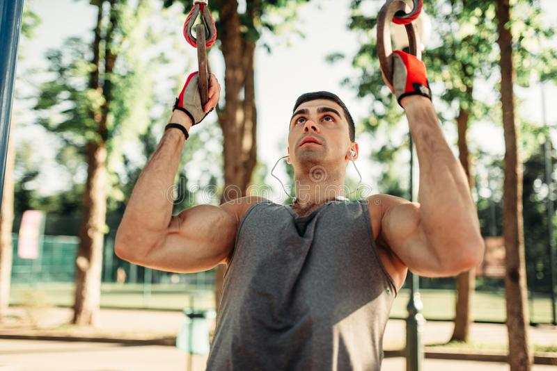Athletic man pulled up on sport rings outdoor royalty free stock images