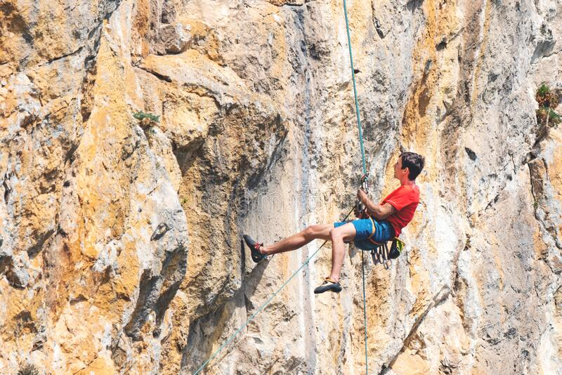 Man Rappelling Down The Rock. Stock Photo - Image of ...