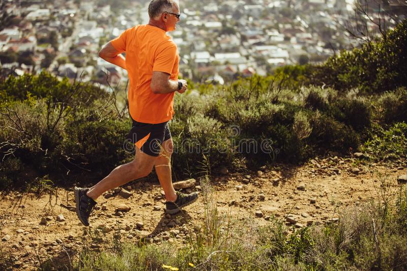 Athletic man running on a hill stock images