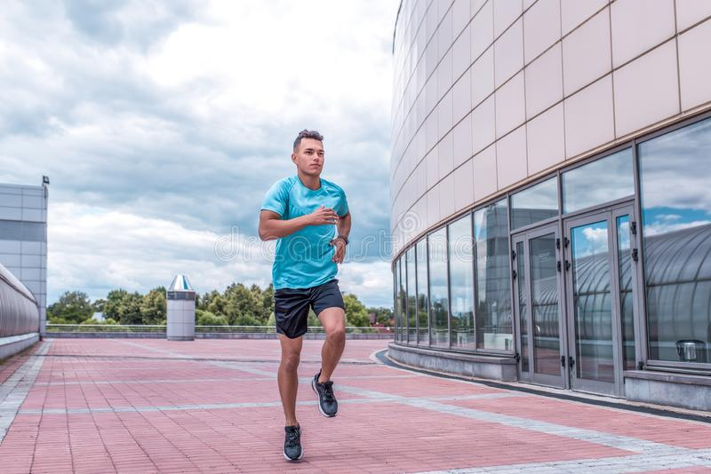 Athletic man running in jump in training, runner in sportswear, training in city during summer, active lifestyle, modern royalty free stock images