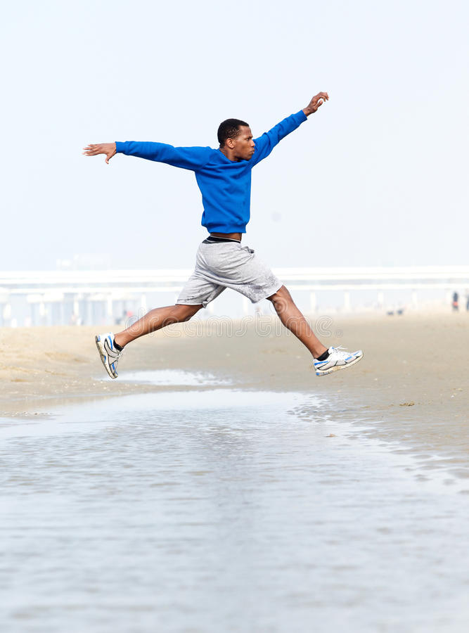 Download Athletic Man Running And Jumping At Beach Stock Photo - Image: 40012414