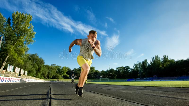 Athletic man running sprint on racetrack. View of sportive man running sprint fastortive man running sprint fast on paved racetrack of athletic field in sunlight stock image