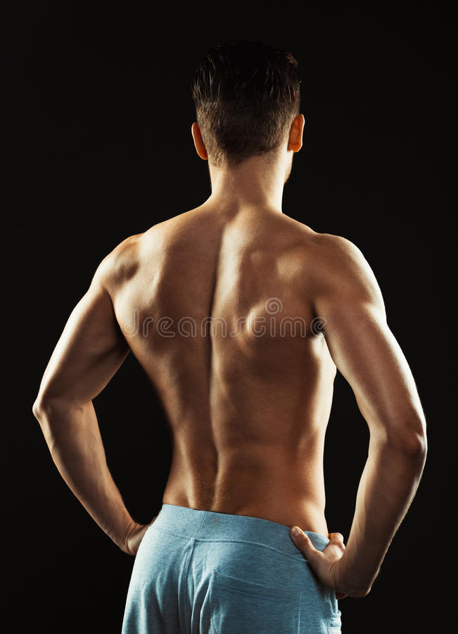 Free Athletic Man Showing His Back On The Black Background Stock Image - 54604011