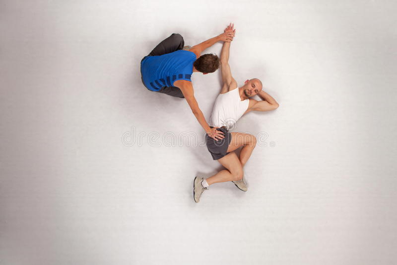 Athletic man streching with personal trainer. Overhead view of streching with personal trainer stock photos