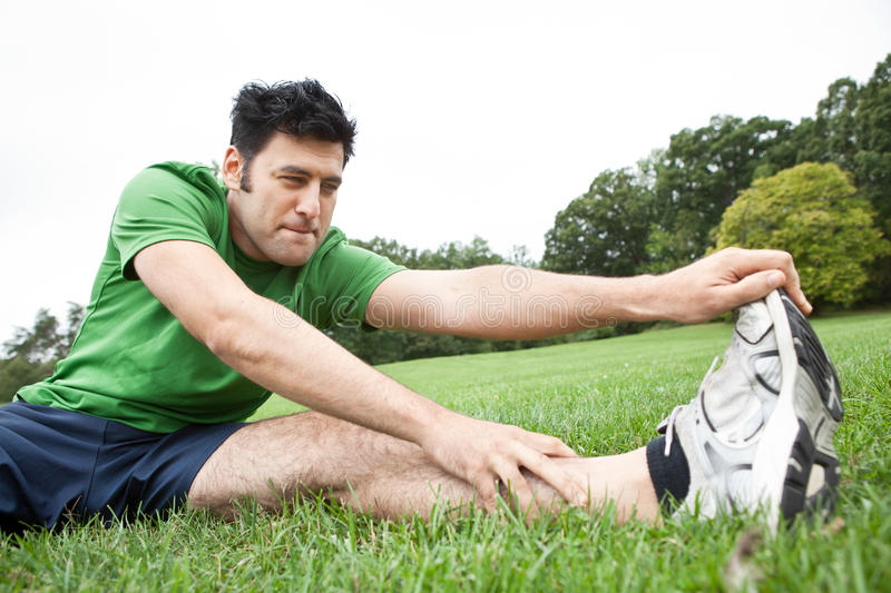 Athletic man stretching leg stock images