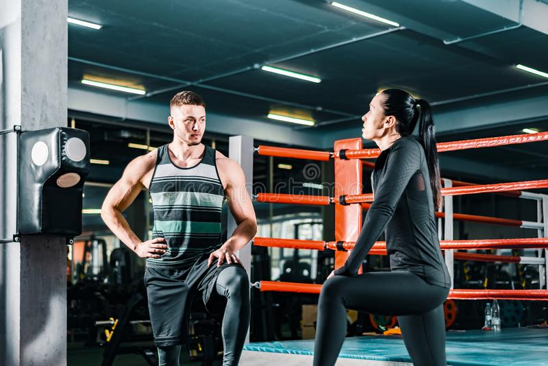 Athletic man talking to a sports woman in the gym. fitness workout. communication between people. stock photos
