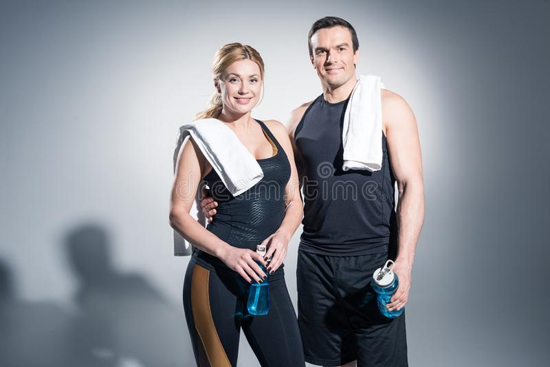 Athletic man and woman with towels holding sport bottles royalty free stock photography