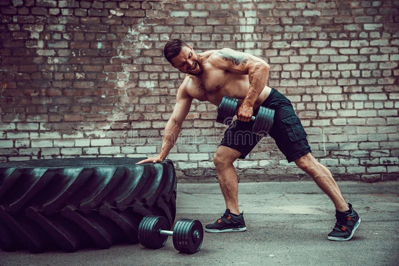 Athletic man working out with a dumbbell. Strength and motivation. Exercise for the muscles of the back. Athletic man working out with a dumbbell in front of stock photo