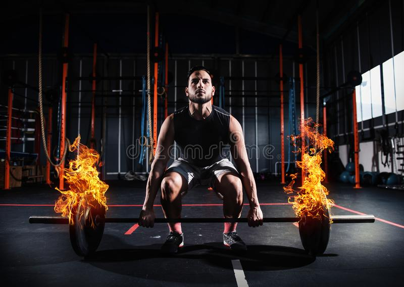 Athletic man works out at the gym with a fiery barbell stock photo