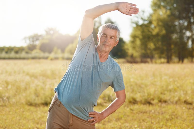 Athletic mature male with fit body, bends aside, does physical exercise outdoor, poses against green field background, breathes fr stock images