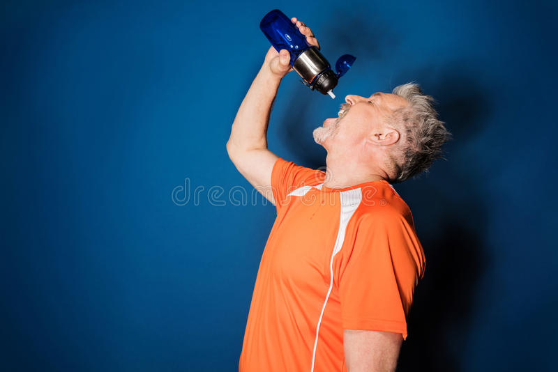 Athletic mature man drinking water from sports bottle royalty free stock image