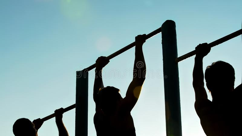 Athletic men doing pull-ups on chin-up bars, preparing for sports competition. Stock photo royalty free stock photos