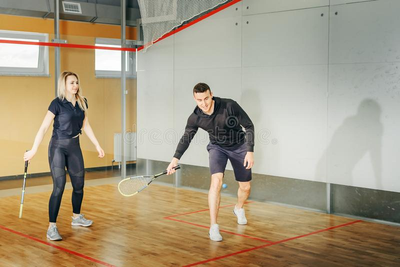 Athletic man and woman playing squash stock photo